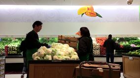 Produce clerk stocking vegetable for sale stock video footage