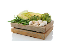Produce Crate with Vegetavles. Wooden Produce crate with assorted vegetables, over a white background with reflection. Items include, corn on the cob, green Stock Photo