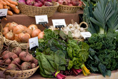 Produce at Local Farmers Market. Beets, onions, garlic, kale, lettuce, leeks, greens, and carrots at a local farmers market Royalty Free Stock Photo
