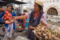 Produce vendor in the Saturday market in Otavalo Ecuador. May 6, 2017 Otavalo, Ecuador: produce vendor in the Saturday market giving change to costumer Stock Photos