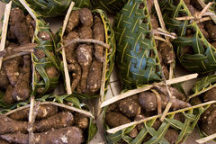 Produce wrapped in palm baskets. Groups of Yams for sale grouped in palm frond woven baskets Royalty Free Stock Image