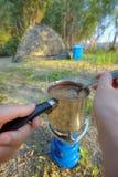 Producendo caffè sul fuoco di accampamento Immagini Stock