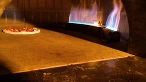 Producendo e cocendo una pizza di merguez fresca da un forno caldo video d archivio