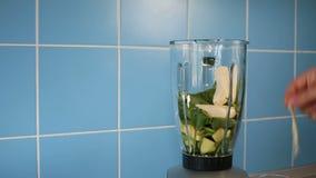 Producendo frullato sano verde in un barattolo di vetro sul miscelatore a casa in cucina archivi video