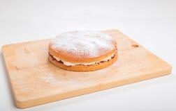 Producendo i pan di Spagna, dolce finito sopra con lo zucchero a velo vagliato Fotografia Stock