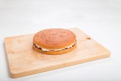 Producendo i pan di Spagna, il dolce finito ha riempito di crema del burro e dell'inceppamento su un bordo di legno Fotografie Stock Libere da Diritti
