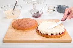 Producendo il pan di Spagna, diffusione di spaccatura del dolce con inceppamento/prerogativa che mette la crema del burro nel rie Fotografia Stock