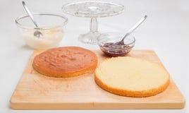 Producendo il pan di Spagna, spaccatura del dolce pronta a mettere riempire Fotografia Stock