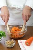 Producendo l'insalata grattata della carota, lanciante un'insalata Fotografia Stock