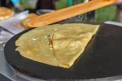 Producendo pancake con il riempimento sulla frittura della cucina elettrica Immagine Stock