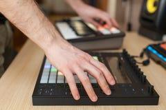 Producent robi muzyce na fachowym produkcja kontrolerze z pchnięcie guzika ochraniaczami fotografia stock