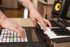 Producenten gör en musik på det MIDI tangentbordet arkivbild