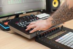 Producenten gör en musik på det MIDI tangentbordet fotografering för bildbyråer