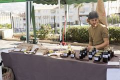 Producer of carob sweet selling at Ecoaltea. Producer of carob sweet selling in a market in Altea, Alicante province in Spain stock photography