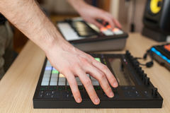Producer makes a music on professional production controller with push button pads. Stock Photography