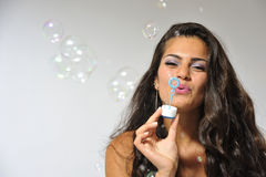 Producing bubbles. Beautifull black haired woman producing soap bubbles. Her face is in focus Royalty Free Stock Photography