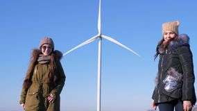 Producing clean renewable energy, lovely girlfriends are walking near windmill and showing finger. In open air stock video