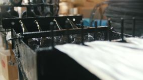 Producing of fiberglass reinforcement - the wire passes through the engine oil. Close up stock video