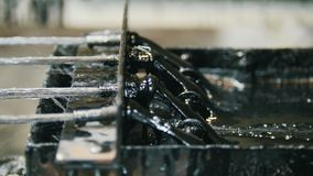 Producing of fiberglass reinforcement - the wire passes through the engine oil - top view. Shot stock video