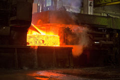 Producing steel in foundry. Shapening molten steel and making it solid before transporting to cooling-off procedure royalty free stock photo