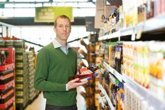 Product Comparison. Portrait of a man comparing two products in a grocery store Royalty Free Stock Photo