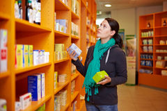 Product comparison in drugstore. Woman making a product comparison in a drugstore stock photo