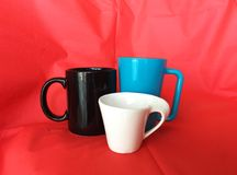 Three coffee or tea cups with red fabric background royalty free stock images