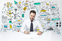 Product placement concept. Attractive young man doing paperwork at workplace with colorful business sketch. Product placement concept Royalty Free Stock Photos