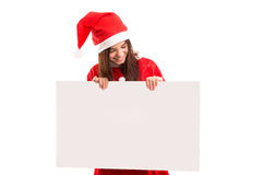 Product presentation. Sexy asian woman dressed as Santa Claus, presenting your product on a white board Royalty Free Stock Photography