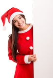 Product presentation. Sexy asian woman dressed as Santa Claus, presenting your product on a white board Royalty Free Stock Images