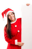 Product presentation. Sexy asian woman dressed as Santa Claus, presenting your product on a white board Royalty Free Stock Image