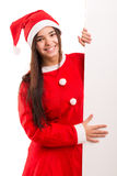 Product presentation. Sexy asian woman dressed as Santa Claus, presenting your product on a white board Stock Photography