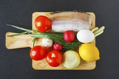Product set for healthy balanced dish on black background. Fresh organic vegetables and fish piece on cutting board. Top view.  Stock Photos