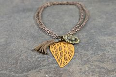 Antique necklace with bronze chain, Green sun shaped pendant and a tin Leaf shaped Pendant. Product shot of an Antique necklace with bronze chain, Green sun royalty free stock photos