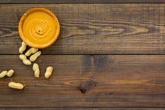Product voor het hartelijke product van de ontbijt hoog-Calorie Pindakaas in kom dichtbij noten in shell op donkere houten achter stock fotografie