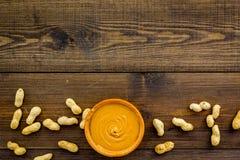 Product voor het hartelijke product van de ontbijt hoog-Calorie Pindakaas in kom dichtbij noten in shell op donkere houten achter stock foto's
