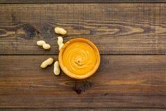 Product voor het hartelijke product van de ontbijt hoog-Calorie Pindakaas in kom dichtbij noten in shell op donkere houten achter royalty-vrije stock afbeelding