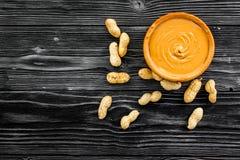 Product voor het hartelijke product van de ontbijt hoog-Calorie Pindakaas in kom dichtbij noten in shell op zwarte houten achterg royalty-vrije stock foto