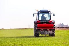 Producteur dans le domaine de blé de fertilisation de tracteur au ressort avec le npk photo stock
