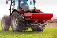 Producteur dans le domaine de blé de fertilisation de tracteur au ressort avec le npk images stock
