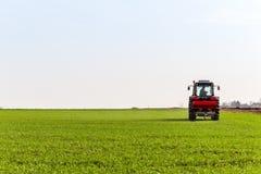 Producteur dans le domaine de blé de fertilisation de tracteur au ressort avec le npk photos stock