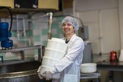 Productie van kaas in zuivelfabriek, arbeider met vormen royalty-vrije stock foto