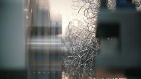 Productie van metaaldelen op de draaibankmachine bij de fabriek, veel metaalspaanders, industrieel concept, profiel stock videobeelden
