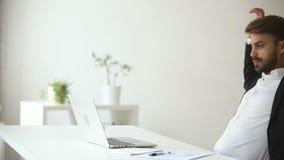 Productieve tevreden zakenman die het achter het eindigen bureauwerk aangaande laptop leunen stock footage