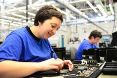 Production and assembly of microelectronics in a hi-tech factory. Older women assembles components Stock Image