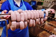 Production of boiled sausages and smoked sausage at a meat factory. Food industry stock photography