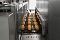 Production of bread at the bakery. Baked Breads on the production line at the bakery Stock Photo