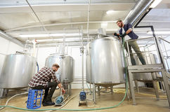 Men working at craft beer brewery kettles. Production, business and people concept - man working with kettles and compressors at craft beer brewery or non Stock Photography