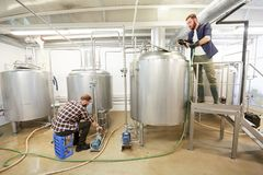 Men working at craft beer brewery kettles. Production, business and people concept - men working with kettles and compressors at craft beer brewery or non Royalty Free Stock Images