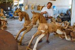 Production of carved wooden animal sculpture. Lampang, Thailand - November 3, 2012: Craftsman polishing wooden horse sculpture with polishing machine for Royalty Free Stock Image